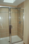 Warm tile colors, trim, glass shower doors