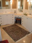 White bath cabinets, warm color flooring
